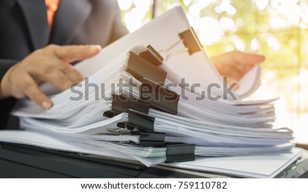 Businessman hands working in Stacks of paper files for searching information on work desk office, business report papers,piles of unfinished documents achieves with clips indoor,Business concept #759110782