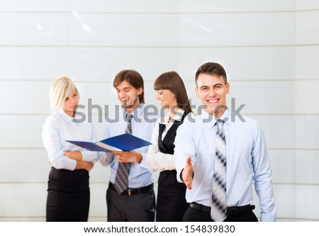 businessman handshake, hold hand shake welcome gesture, Handsome young excited business man happy smile at conference hall over group of businesspeople working background, people meeting