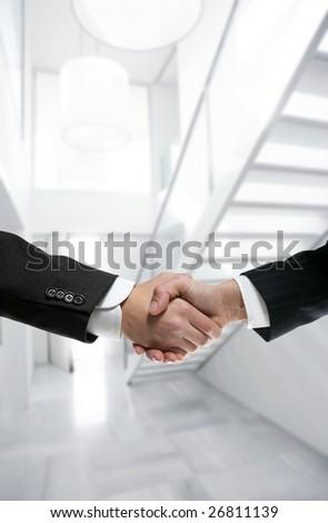 Businessman handshake on modern white stairway office [Photo Illustration]