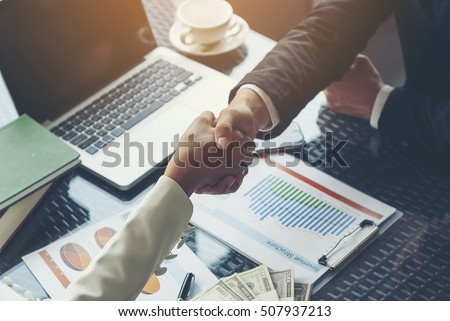 Photo of  Businessman handshaking for business cooperation, Chart documents showing income structure and a laptop, along with a large number of banknotes placed on the table for signing commercial contracts.