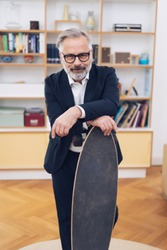 Businessman hankering after his vacation or weekend relaxation standing in his suit in the office leaning on a skate board with a smile