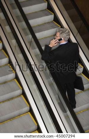 Businessman has a mobile phone conversation while riding the escalator. Vertical shot.