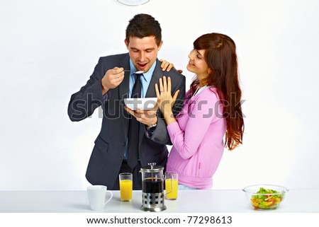 Businessman has breakfast before go to work and his wife standing near him and hugging him