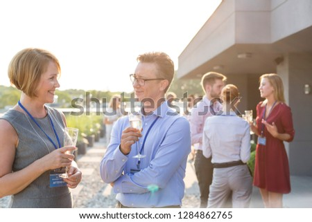 Businessman have an intellectual conversation with his secretary on the balcony at their corporate business retreat they are both sharing a glass of wine and their colleagues are in the background