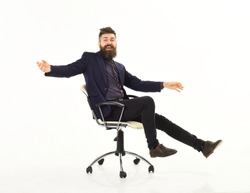 Businessman having fun. Cheerful businessman sitting on the office chair with his arms raised while isolated on white