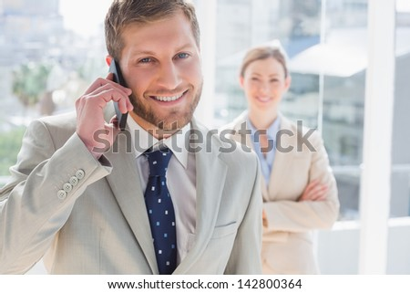 Businessman having phone conversation and smiling at camera with colleague standing behind him