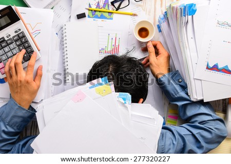 Shutterstock Businessman heavy workload sleep at office desk with finance sheet calculator and coffee.(concept for overworked)
