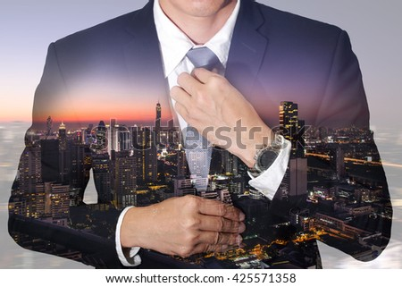 Businessman held necktie dress to look good and night city as preparation and leadership concept. #425571358