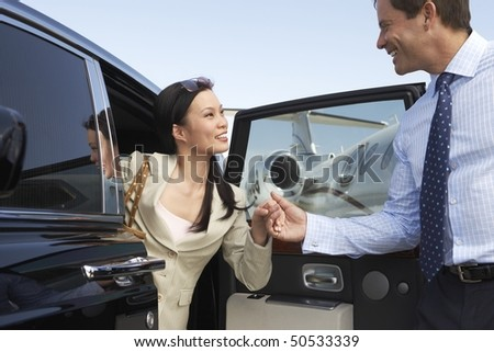 Businessman helping Woman Get Out of Car parked near private jet, side view