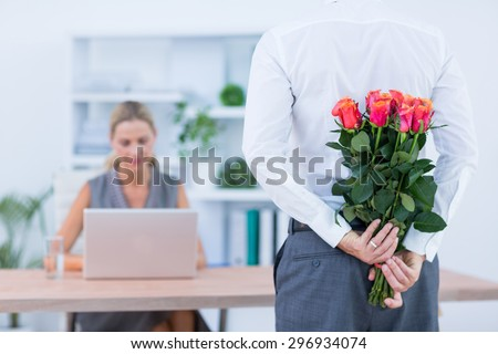 Businessman hiding flowers behind back for colleague in the office