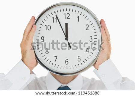 Businessman hiding his face with a wall clock