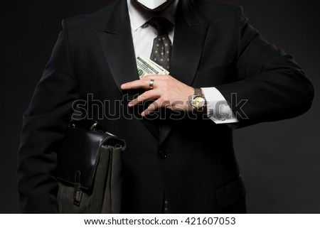 Businessman hiding money in jacket pocket. Corruption and fraud concepts. Man in business suit posing with black briefcase. ストックフォト ©