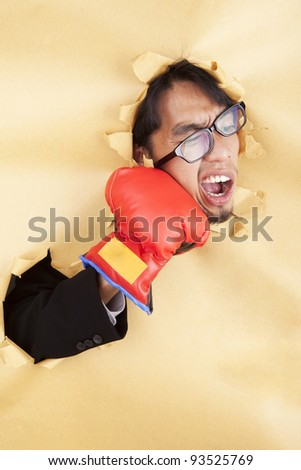 Businessman hitting himself with a red boxing glove in the face