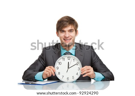Businessman hold clock, sitting at the desk, handsome young business man happy smile,  wear elegant suit and tie isolated over white background