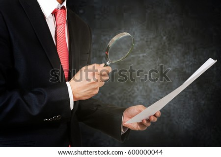 businessman hold magnifying glass and investigate documents