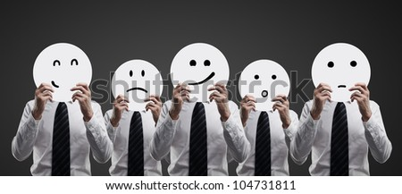 businessman hold plates with smilies on black background