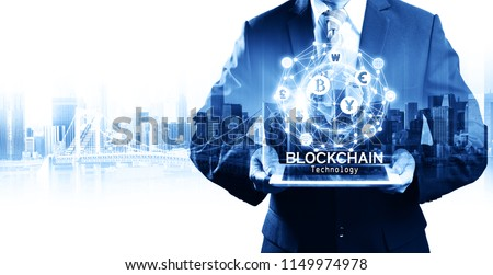 Businessman hold the blockchain hologram on tablet, Business and Technology, Internet of thinks and network the concept of cryptocurrency, blockchain