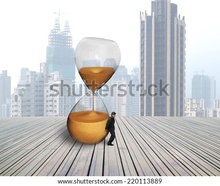 businessman hold the inclined hourglass on wooden floor with city skyscraper
