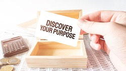 Businessman hold white card with text discover your purpose Calculator,wood box,money and financial documents