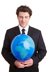 Businessman holding a balloon with a world globe printed on it