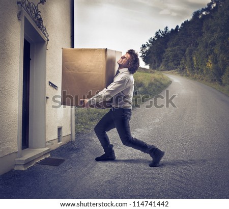 Businessman holding a big box near a house