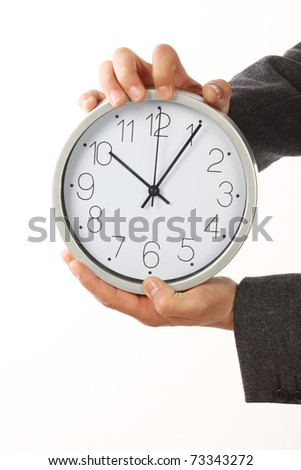 Businessman holding a big clock. Time for  work concept