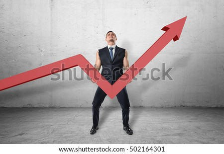 Businessman holding a big red line graph with an upturned arrow and trying to raise it up with his muscular arms. Working hard to increase incomes. Making efforts to grow profits. Improving business