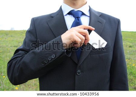 Businessman holding a blank card from his pocket - stock photo