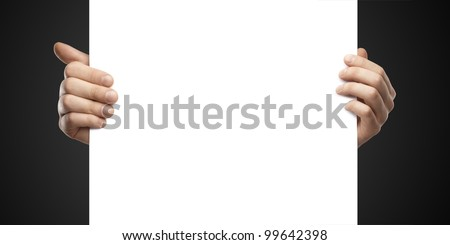 Businessman holding a blank white board. Male hands holding a blank white panel. On a black background