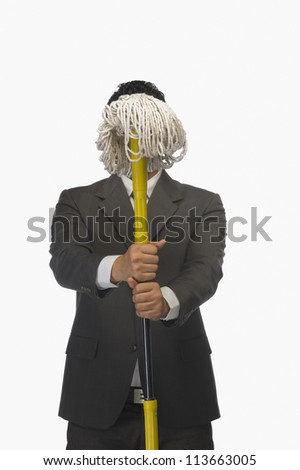 Businessman holding a broom in front of his face