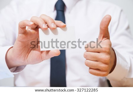 Businessman holding  a business card and showing a thumb up sign - closeup shot