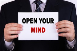 Businessman holding a card with text open your mind