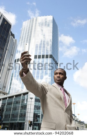 Businessman holding a cell phone while standing in the financial district.