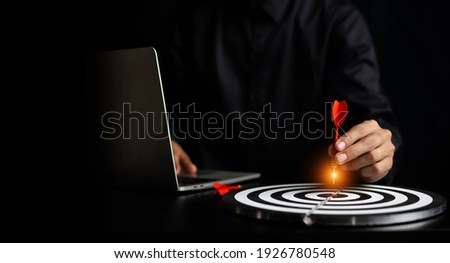 Businessman holding a darts aiming at the target center business goal concept  Foto stock ©