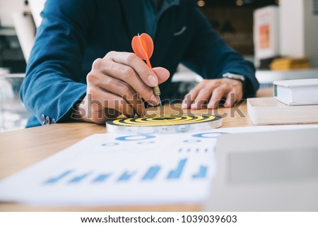 Businessman holding a darts aiming at the target center business goal concept - business targeting, aiming, focus concept,metaphor to target marketing or target arrow concept.