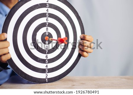 Businessman holding a darts aiming at the target center business goal concept - business targeting, aiming, focus concept,metaphor to target marketing or target arrow to business success concept.