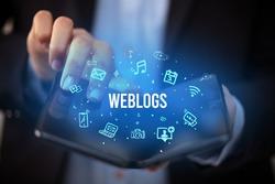 Businessman holding a foldable smartphone with WEBLOGS inscription, social media concept