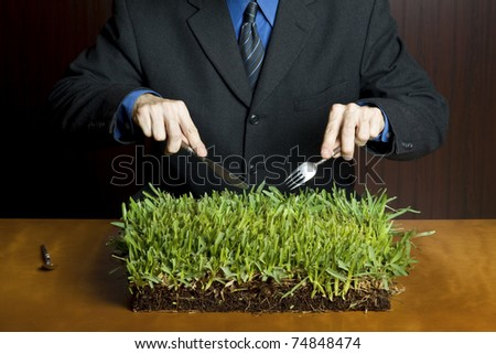 Businessman holding a fork and knife cutting into a plate of grass