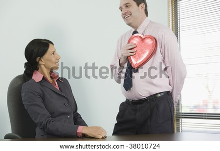 Businessman holding a heart shaped gift in front of a businesswoman
