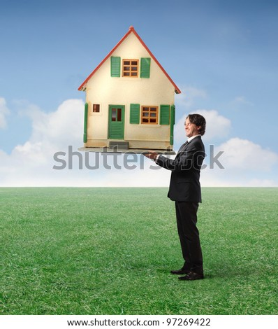 Businessman holding a house in his hands on a green meadow