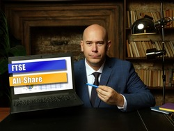 Businessman holding a laptop. Business concept about Financial Times and Stock Exchange FTSE All-Share with phrase on the sheet.