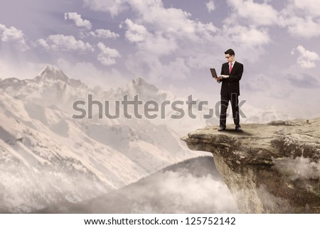 Businessman holding a laptop on top of a mountain under cloudy sky