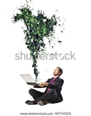 Businessman holding a laptop with green paint coming out from it
