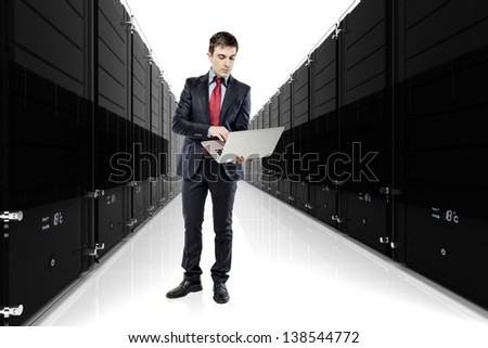 businessman holding a laptop with servers in the background
