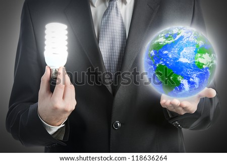 Businessman holding a light bulb and planet Earth. Elements of this image furnished by NASA