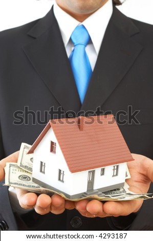 businessman holding a mini house and US dollars