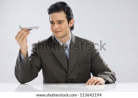Businessman holding a model airplane - stock photo