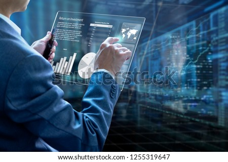 Businessman holding a modern tablet touch screen analysing on investment risk management and return on investment analysis or business performance.