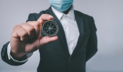 Businessman holding a navigation compass in hand with copy space background. business planning and Business navigate recovery for businessmen to resume business growth in the economic crisis
