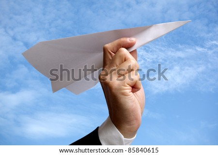 Businessman holding a paper plane ready to launch into the sky, concept for aspirations and dreams - stock photo